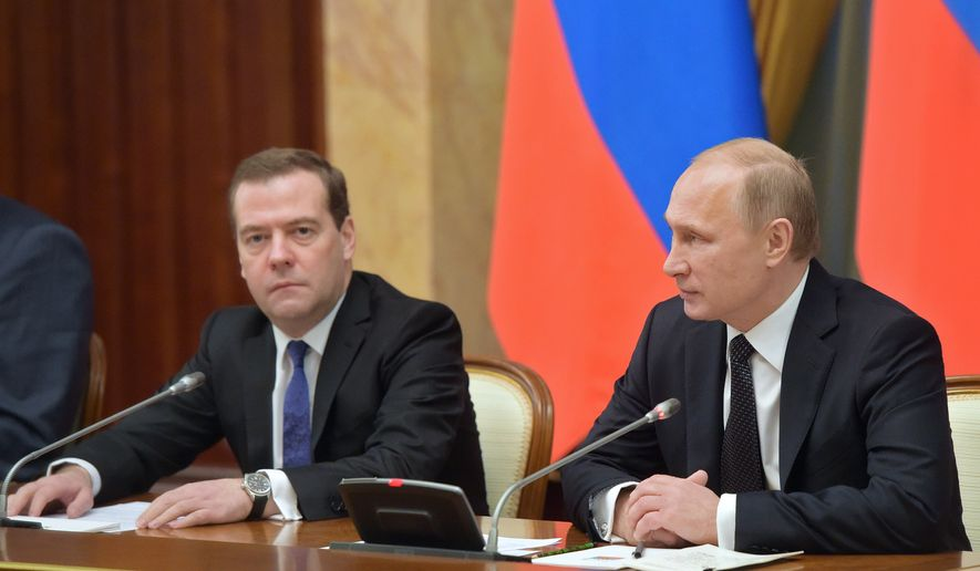 Russian President Vladimir Putin, right, and Prime Minister Dmitry Medvedev lead a cabinet meeting in Moscow, Russia, Thursday, Dec. 25, 2014. (AP Photo/RIA-Novosti, Alexander Astafyev, Government Press Service)