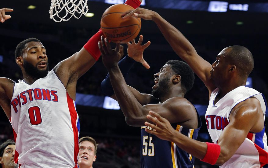Detroit Pistons center Andre Drummond (0) and Detroit Pistons guard Jodie Meeks, right, defend against Indiana Pacers center Roy Hibbert (55) in the first half of an NBA basketball game in Auburn Hills, Mich., Friday, Dec. 26, 2014. (AP Photo/Paul Sancya)