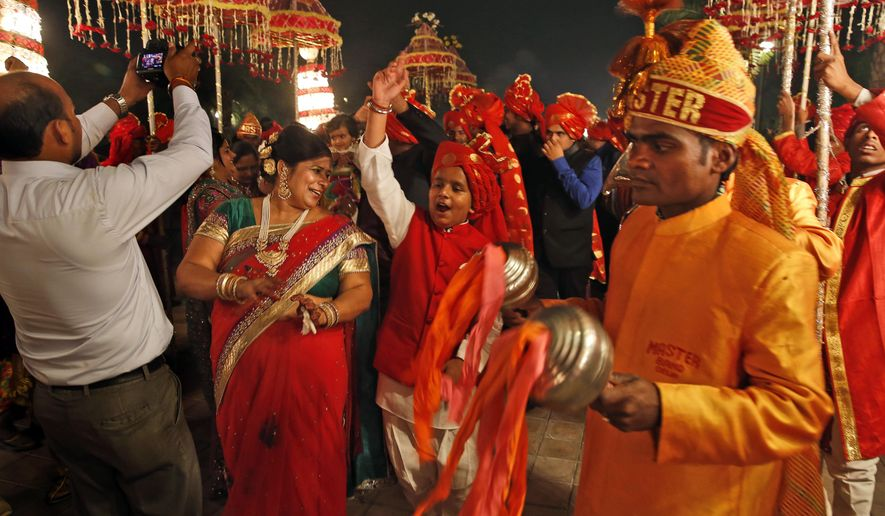 In this Nov. 3, 2014 photo, members of Indian Brass band, play as they accompany a wedding procession, in New Delhi, India. The wedding season is in full swing in India, marking what should be the busiest time of year for the traditional brass bands that lead raucous processions announcing the arrival of the bridegroom to the neighborhood. Dressed in faded military-style uniforms or long silken tunics and turbans, brass bands playing the latest Bollywood tunes have long been a must-have at any Indian wedding. But as the tastes of young, wealthier Indians shift to more modern music, young couples increasingly choose DJs playing electronic music instead of live bands. The shift is leaving band owners and musicians struggling to find gigs, exacerbating an already difficult existence. (AP Photo /Manish Swarup)