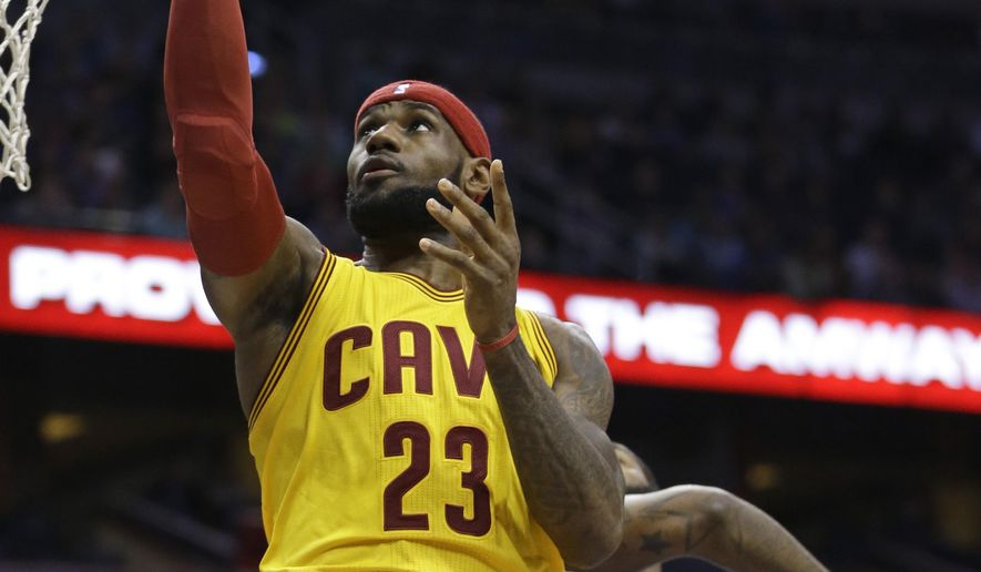 Cleveland Cavaliers' LeBron James (23) makes a basket as he gets past Orlando Magic's Kyle O'Quinn, back right, during the first half of an NBA basketball game, Friday, Dec. 26, 2014, in Orlando, Fla. (AP Photo/John Raoux)