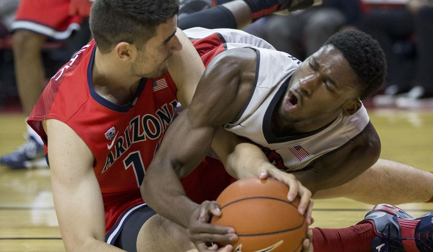 Arizona center Dusan Ristic, left, and UNLV center Goodluck Okonoboh fight for the ball during the first half of an NCAA college basketball game Tuesday, Dec. 23, 2014, in Las Vegas.  (AP Photo/Eric Jamison)