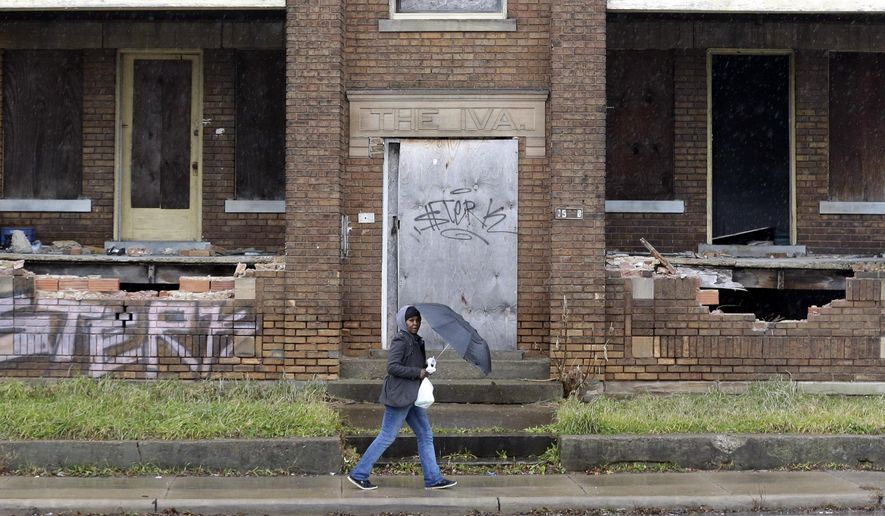 In this Dec. 16, 2014 photo, a woman walks past a dilapidated building in East Cleveland, Ohio. This impoverished Cleveland suburb is considering filing a municipal bankruptcy, making it the first city in Ohio since bankruptcy laws were established in 1934, to do so. (AP Photo/Tony Dejak)