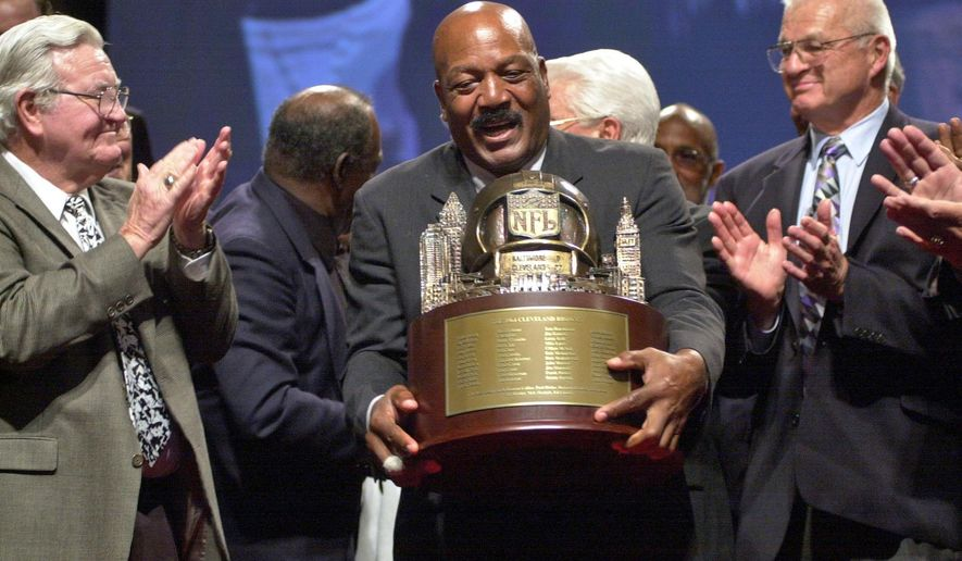 FILE - In this Sept. 10, 2004, file photo, Hall of Famer Jim Brown, center, picks up a trophy presented by NFL Commisioner Paul Tagliabue, to the members of Cleveland Browns 1964 Championship Team at Severance Hall in Cleveland. At left is Bernie Parish, and at right Paul Wiggin. The original trophy presented to the team after their 1964 victory over the Baltimore Colts is in the possession of the Green Bay Packers, who were the 1965 Championship Team. Saturday marks 50 years since the Browns won the NFL title, the last championship for this city's three pro sports franchises. For fans, it's been mostly misery since. That's why LeBron James' return provides something dearly needed: hope. (AP Photo/Jamie-Andrea Yanak, File)
