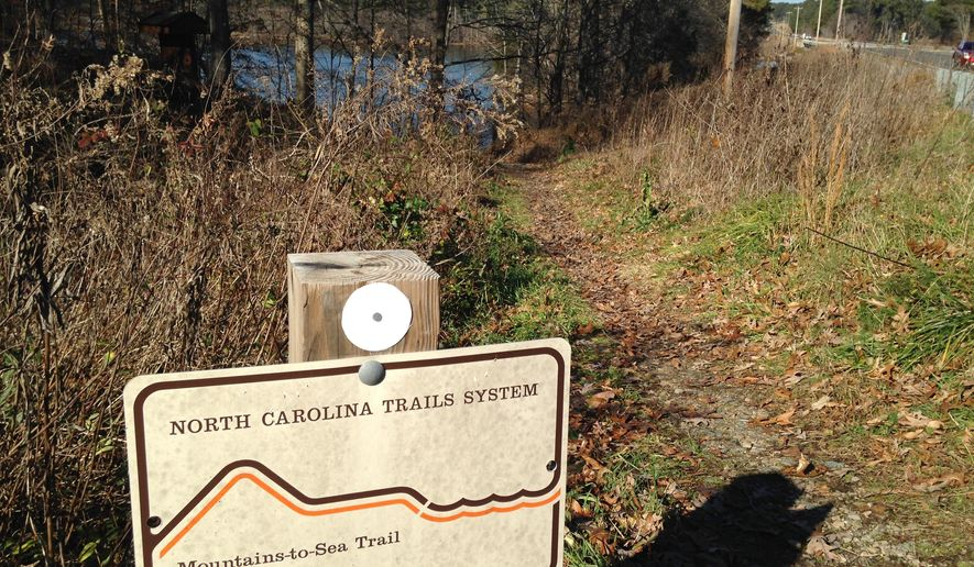In this Thursday, Dec. 18, 2014 photo, a sign marking a trail head for the Mountains-to-Sea trail is seen near Falls Lake in Wake Forest, N.C.  Efforts to boost the 1,000-mile trail in 2015 include a master plan commissioned by North Carolina, a comprehensive hiking guide and trail additions in several cities. (AP Photo/Jonathan Drew)