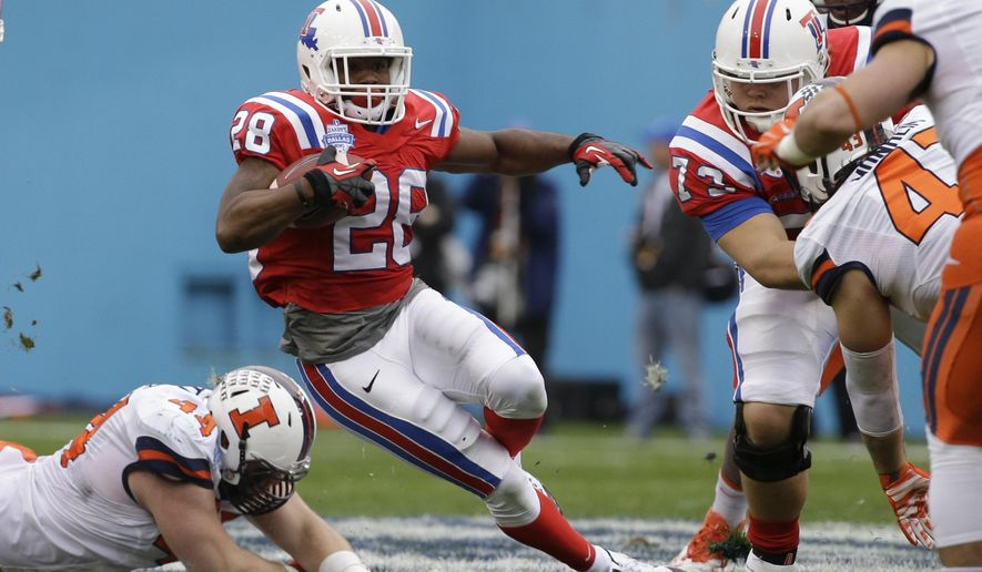 Louisiana Tech running back Kenneth Dixon (28) beats a tackle against Illinois defensive lineman Austin Teitsma (44) and finds a hole to run as Louisiana Tech Kirby Wixson (73) blocks Illinois Mason Monheim (43) during the first half of the Heart of Dallas Bowl NCAA college football game Friday, Dec. 26, 2014, in Dallas. (AP Photo/LM Otero)