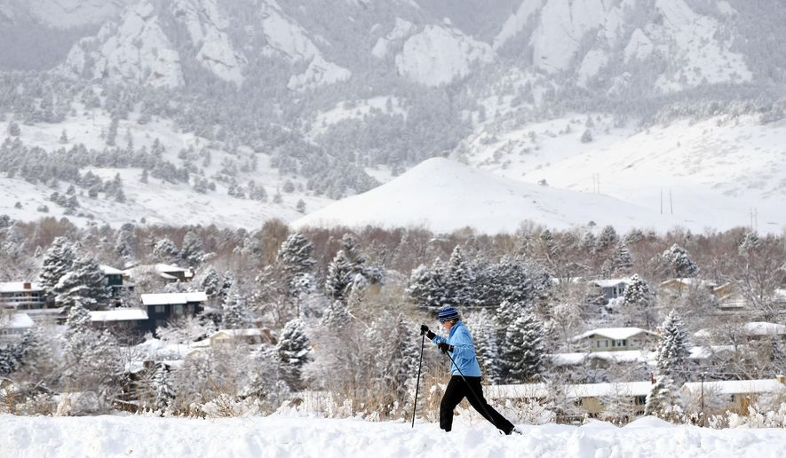 A woman cross country skis amid fresh snow past a residential neighborhood in Boulder, Colo., Friday, Dec. 26, 2014. Parts of Colorado's mountains and plains are getting more snow, but the Christmas storm is tapering off in the Denver area. (AP Photo/Brennan Linsley)