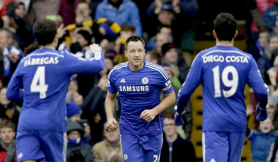 Chelsea's captain John Terry, center, celebrates scoring his side's first goal with his teammates Cesc Fabregas, left, and Diego Costa during the English Premier League soccer match between Chelsea and West Ham at Stamford Bridge stadium in London, Friday, Dec. 26, 2014.  (AP Photo/Matt Dunham)