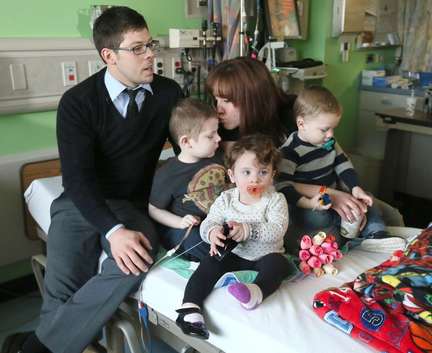 In this photo taken on Thursday, Dec. 25, 2014, William and Sarah Cramer, of Mogadore, Ohio sit with their children, from left,  Billy, 4, Delaney, 1, and Mason, 2, during a television interview after their wedding in Billy's hospital room at Akron Children's Hospital, in Akron, Ohio. The Ohio couple who married on Christmas Day decided to share their vows in the hospital room where their 4-year-old son, Billy, is being treated for cancer.  (AP Photo/Akron Beacon Journal, Phil Masturzo) MANDATORY CREDIT