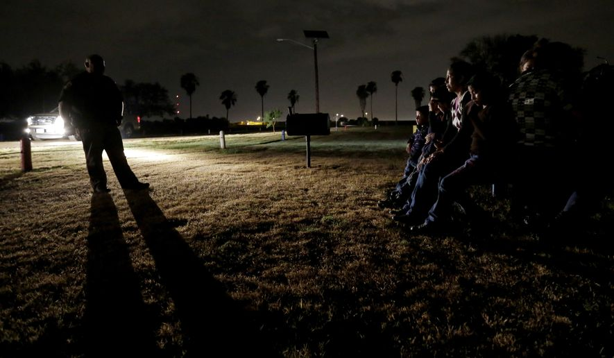 In this June 25, 2014, file photo, a group of immigrants from Honduras and El Salvador, who crossed the U.S.-Mexico border illegally, are stopped in Granjeno, Texas. The Homeland Security Department is experimenting with a new way to track immigrant families caught crossing into the U.S. illegally then released: GPS-enabled ankle bracelets. (AP Photo/Eric Gay, File)