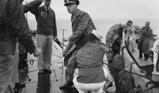 Rear Adm. Hyman G. Rickover, father of nuclear powered submarines, boards the USS Nautilus from the Navy Tug 534 in the Narrows below Brooklyn, New York on August 25, 1958. Cdr. William Anderson, head showing at left, awaits to greet the admiral aboard the U.S. Navy's first nuclear sub. Anderson is skipper of the Nautilus. Saluting at left center is Lt. Donald P. Hall, gunnery officer of the Nautilus. The craft returned earlier from four-month voyage. (AP Photo/Pool)