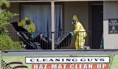 In this Oct. 3, 2014 file photo, hazardous material cleaners prepare to hang black plastic outside the apartment where Thomas Eric Duncan, the Ebola patient who traveled from Liberia to Dallas, stayed, in Dallas. Duncan's fiancé, Louise Troh, who lived in the residence, is grieving Duncan's fatal bout with Ebola and trying to help her family refocus on the future. Neither has been easy. So far, finding a landlord willing to take them in has been elusive. (AP Photo/LM Otero, File)
