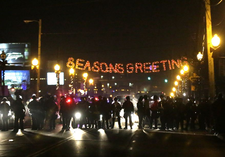 Protesters gather near the Ferguson Police Department, Wednesday, Nov. 25, 2014, in Ferguson, Mo. Missouri's governor ordered hundreds more state militia into Ferguson on Tuesday, after a night of protests and rioting over a grand jury's decision not to indict police officer Darren Wilson in the fatal shooting of Michael Brown, a case that has inflamed racial tensions in the U.S. (AP Photo/Charlie Riedel)