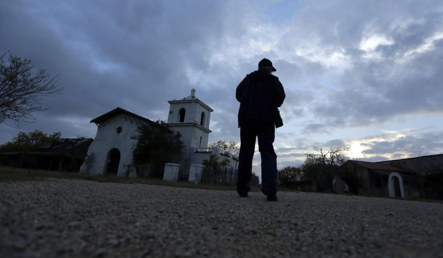 "In this Dec. 4, 2014 photo, Rich Curilla walks past a replica of the San Fernando Cathedral, built for John Wayne's 1960 movie ""The Alamo,"" in Brackettville, Texas. The movie set includes a full-scale re-creation of the Alamo compound. (AP Photo/Eric Gay)"