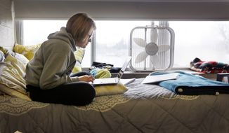 In this Dec. 9, 2014, photo, Adrian College student Abby Slusher studies in her dorm in Adrian, Mich. The small, private Michigan college has got a deal for you: Make at least $37,000 a year after graduating or else the school will pay all or part of your loan. Adrian College has taken out an insurance policy costing about $1,100 on each student starting with this year's freshmen. (AP Photo/Carlos Osorio)