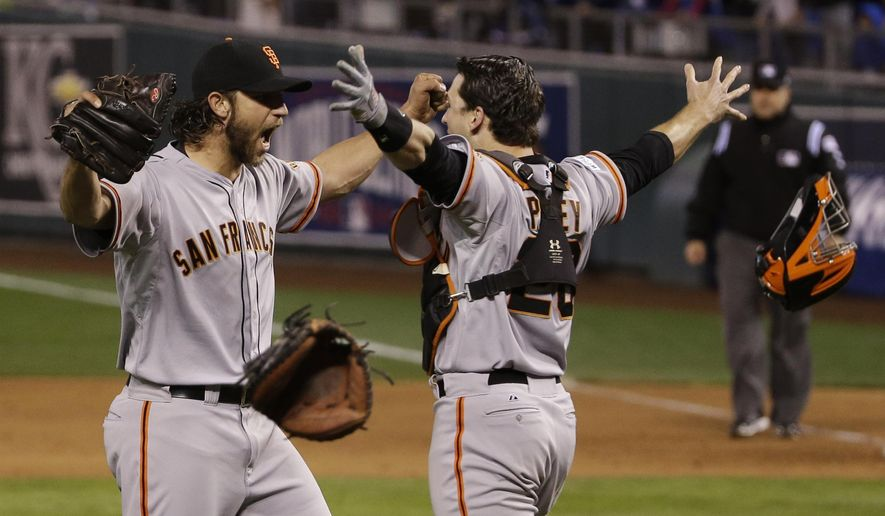 FILE - In this Oct. 29, 2014, file photo, San Francisco Giants pitcher Madison Bumgarner, left, and Buster Posey celebrate after winning 3-2 to win the series over Kansas City Royals after Game 7 of baseball's World Series in Kansas City, Mo. (AP Photo/Matt Slocum, File)
