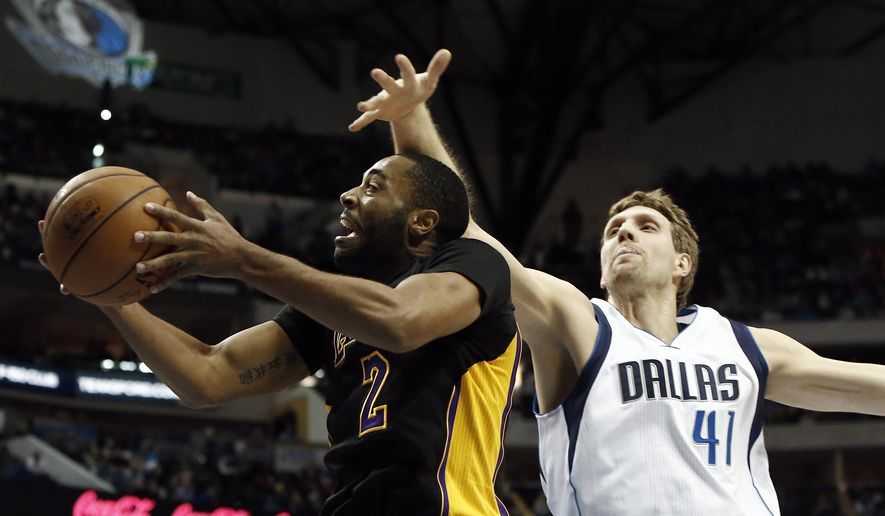 Los Angeles Lakers guard Wayne Ellington (2) attempts a layup as Dallas Mavericks forward Dirk Nowitzki (41) defends in the first half of an NBA basketball game, Friday, Dec. 26, 2014, in Dallas, Texas. (AP Photo/Brandon Wade)
