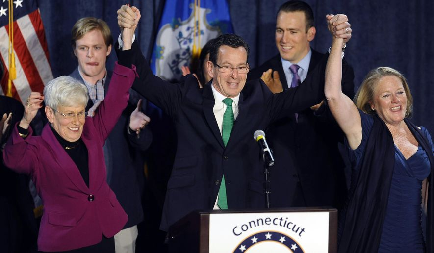 FILE - In this Nov. 5, 2014, file photo, incumbent Democratic Gov. Dannel P. Malloy, raises his arms over his head with Lt. Gov. Nancy Wyman, left, and his wife Cathy Malloy, right, to celebrate his reelection victory in Hartford, Conn. (AP Photo/Jessica Hill, File)