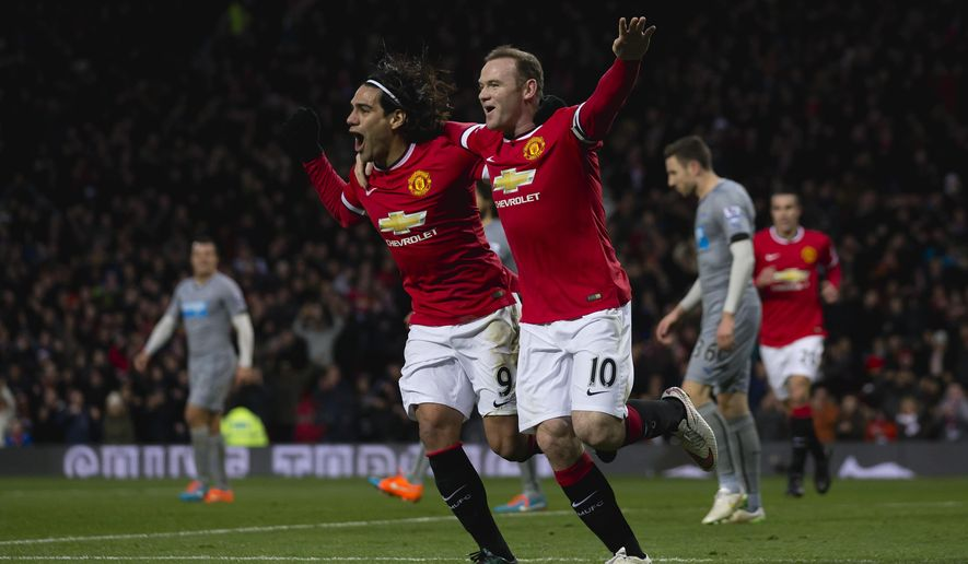 Manchester United's Wayne Rooney, center right, celebrates with teammate Radamel Falcao after scoring during the English Premier League soccer match between Manchester United and Newcastle at Old Trafford Stadium, Manchester, England, Friday, Dec. 26, 2014. (AP Photo/Jon Super)