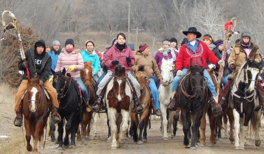 Tim LaBatte, of Peever, S.D., front second from right, Christmas Day, Thursday, Dec. 25, 2014, in Nicollet County, Minn., with dozens of horseback riders on a 330-mile Dakota 38 Plus 2 Memorial Ride from Lower Brule, S.D. to Mankato, Minn. Several hundred ride participants from the United States and Canada rode and drove the route. (AP Photo/The Journal of New Ulm, Fritz Busch)