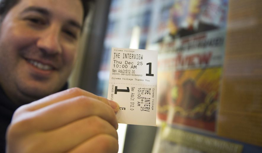 "FILE - In this Dec. 25, 2014 file photo, Derek Karpel holds his ticket to a screening of ""The Interview"" at Cinema Village movie theater, in New York. The film raked in just over $1 million in ticket sales from 331 locations for an impressive $3,142 per theater average, according to distributor Sony Pictures. (AP Photo/John Minchillo, File)"