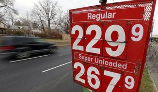 In this Dec. 18, 2014 file photo, a car passes the price of gas at the Eastcoast filling station in Pennsauken N.J. Average gas prices nationwide have dropped to $2.32 a gallon in 2014, down roughly a dollar from a year ago, according to AAA. (AP Photo/Matt Rourke, File)