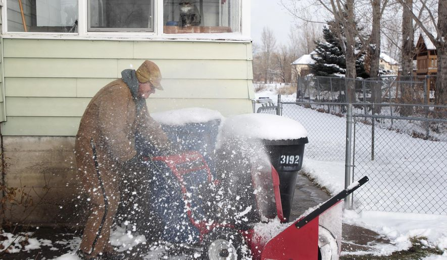 Leonard Baxter, of Provo, uses a snow blower to clear snow from his driveway at his home in Provo, Utah, on Friday, Dec. 26, 2014.(AP Photo/The Daily Herald, Ian Maule)