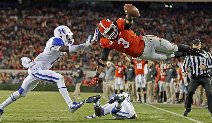 FILE - In this Nov. 23, 2013, file photo, Georgia running back Todd Gurley (3) dives into the end zone for a touchdown as Kentucky cornerback Jaleel Hytchye, left, defends in the first half of an NCAA college football game in Athens, Ga. Georgia coach Mark Richt says junior running back Gurley has informed him that he plans to enter the NFL draft. Richt made the announcement after practice Friday, Dec. 26, 2014, for the Belk Bowl. (AP Photo/John Bazemore, File)