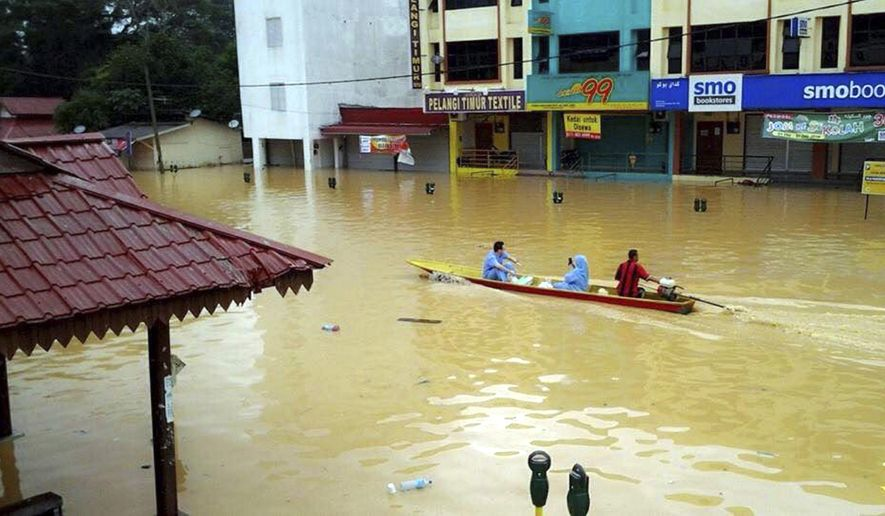 In this Wednesday, Dec. 24, 2014 photo, residents using a boat pass by flooded shops in Kuala Krai, Kelantan state, Malaysia. Malaysian Prime Minister Najib Razak said Friday, Dec. 26, 2014 he was cutting short his U.S. vacation to deal with the worst floods in the country in decades that have killed five people and displaced more than 100,000. (AP Photo) MALAYSIA OUT, NO SALES, NO ARCHIVE