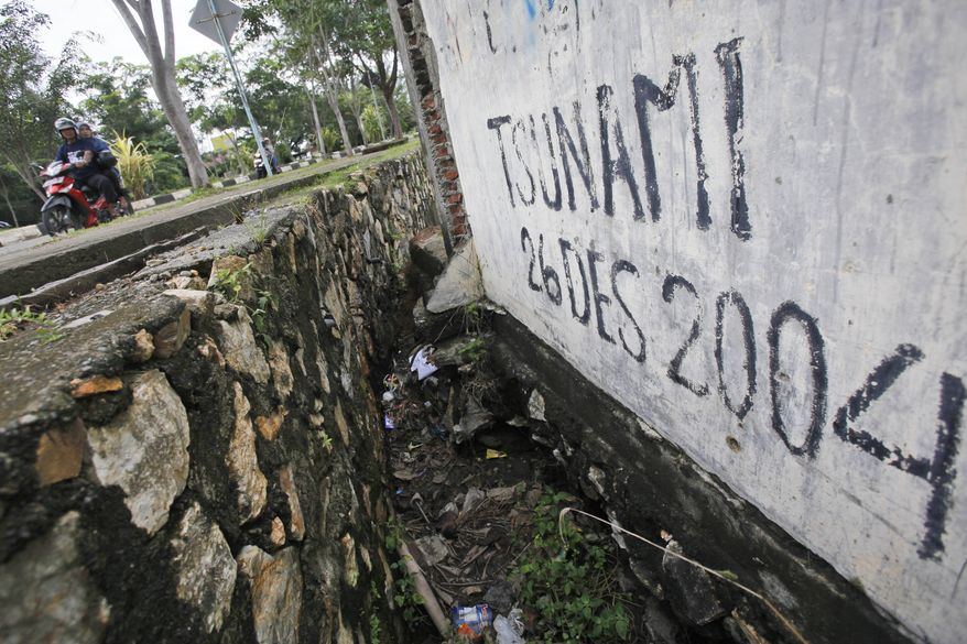 Motorists ride past graffiti with the date of  the Indian Ocean tsunami, in Banda Aceh, Aceh province, Indonesia, Friday, Dec. 26, 2014. The devastating Boxing Day tsunami in 2004 struck a dozen countries around the Indian Ocean rim, killing 230,000 people, most of them in Aceh. (AP Photo/Binsar Bakkara)