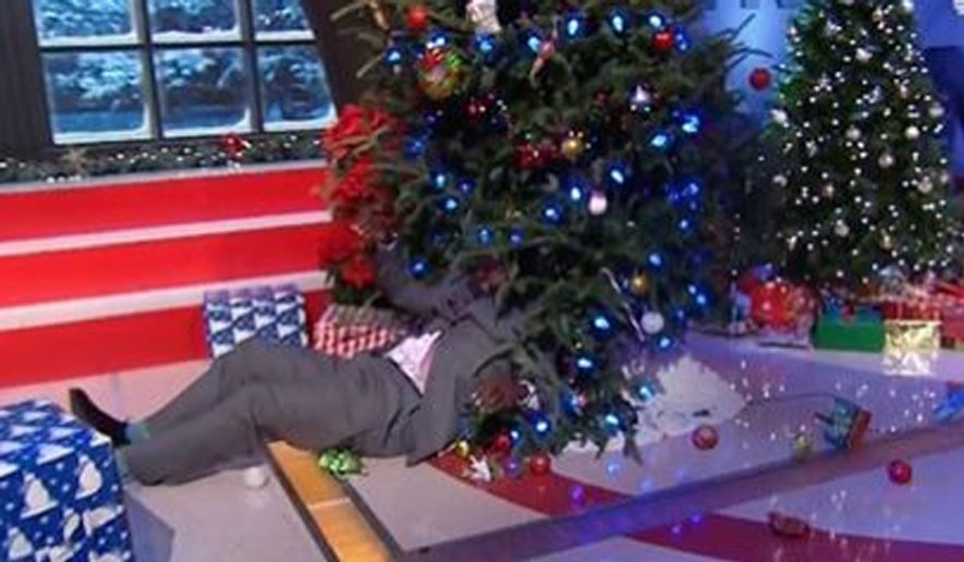 "Shaquille O'Neal pulls himself out from under a Christmas tree during a broadcast of ""The NBA on TNT,"" Dec. 25, 2014. (TNT screenshot)"
