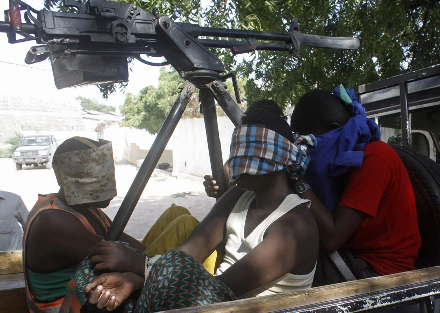 Suspected Al-Shabab militant captured during Thursday's attack on African Union base are seen in Mogadishu, Somalia, in this Thursday, Dec. 25, 2014. (AP Photo/Farah Abdi Warsameh)