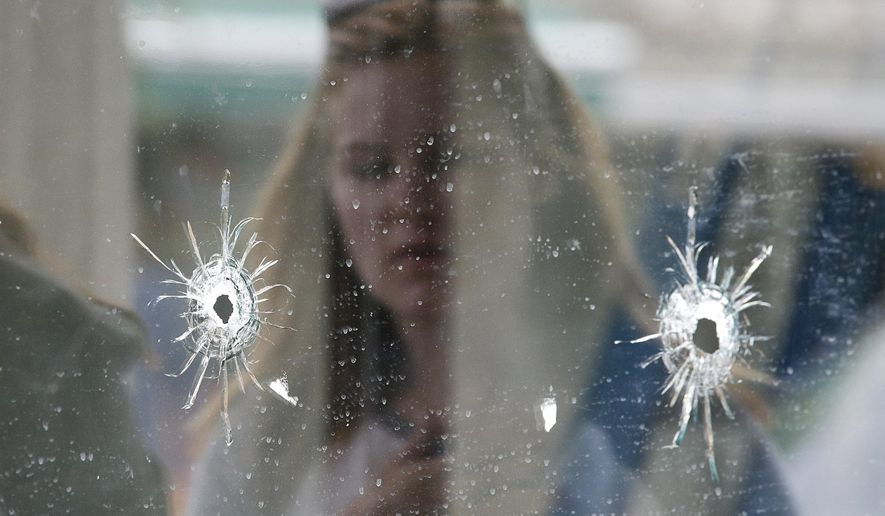 FILE - In this May 24, 2014 file photo, a woman looks at the bullet holes on the window of IV Deli Mark where a mass shooting took place near the University of California, Santa Barbara campus, in the Isla Vista beach community of Santa Barbara, Calif.  In response to the killing rampage of Elliot Rodger, 22, that left seven people, including himself, dead, lawmakers approved and Gov. Jerry Brown signed a law which requires law enforcement agencies to develop policies that encourage officers to search the state's database of gun purchases as part of routine welfare checks.  More than 900 laws approved by the Legislature and signed by the governor will take Jan. 1, 2015. (AP Photo/Jae C. Hong, file)