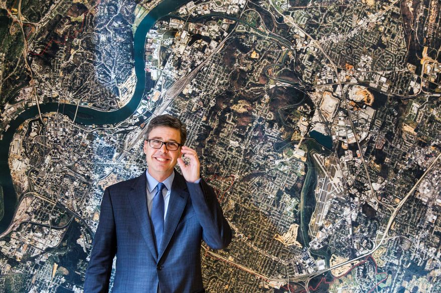 In this Nov. 17, 2014, photo, Chattanooga, Tenn. Mayor Andy Berke stands in front of an aerial image of Chattanooga, on the wall of his conference room. Berke is a major promoter of the city's municipal fiber optic network that provides Internet speeds at more than 50 times the national average. (AP Photo/Erik Schelzig)