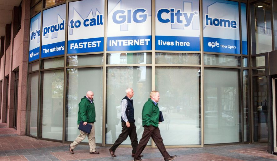 Men walk by a sign in Chattanooga, Tenn., promoting it as Gig City. The city's municipal fiber optic network provides Internet speeds at more than 50 times the national average. (AP Photo/Erik Schelzig)