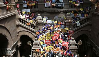 FILE - In this June 17, 2014 file photo, people rally for an increase in the minimum wage on the Great Western Staircase at the Capitol in Albany, N.Y. With the Assembly remaining in control of downstate Democrats and the Senate is now more firmly in the hands of upstate and Long Island Republicans, the New York Legislature is likely looking at stalemate in 2015, when it comes to boosting the minimum wage beyond its next two incremental increases. (AP Photo/Mike Groll, File)