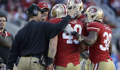 San Francisco 49ers fullback Bruce Miller, center, is congratulated by head coach Jim Harbaugh, left, and running back Alfonso Smith (38) after scoring on a 3-yard touchdown reception against the Arizona Cardinals during the third quarter of an NFL football game in Santa Clara, Calif., Sunday, Dec. 28, 2014. (AP Photo/Marcio Jose Sanchez)