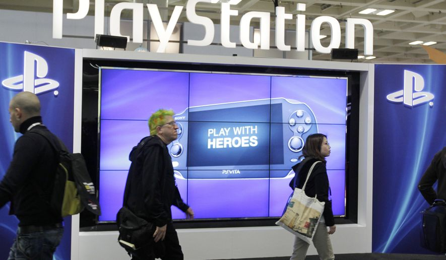 FILE- This March 8, 2012 file photo shows attendees walking past the Sony PlayStation PS Vita console on display in the Sony PlayStation booth at the Game Developers Conference in San Francisco. Sony says its PlayStation Network is back online after three days of disruptions that began on Christmas. But heavy traffic might continue to cause problems for customers seeking to play their favorite games, the company said Sunday, Dec. 28, 2014. (AP Photo/Paul Sakuma, File)