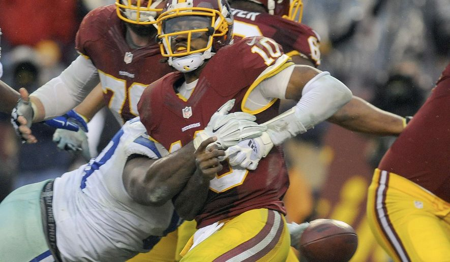 Washington Redskins quarterback Robert Griffin III (10) is sacked by Dallas Cowboys defensive tackle Terrell McClain and fumbles the ball, resulting in a turnover touchdown by Cowboys defensive end Anthony Spencer, during the second half of an NFL football game in Landover, Md., Sunday, Dec. 28, 2014. The Cowboys won 44-17. (AP Photo/Richard Lipski)