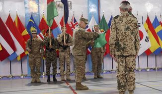 Commander of the International Security Assistance Force (ISAF), Gen. John Campbell, center, cases the ISAF flag during a ceremony at the ISAF headquarters in Kabul, Afghanistan, Sunday, Dec. 28, 2014. The United States and NATO formally ended their war in Afghanistan on Sunday with the ceremony at their military headquarters in Kabul as the insurgency they fought for 13 years remains as ferocious and deadly as at any time since the 2001 invasion that unseated the Taliban regime following the Sept. 11 attacks. (AP Photo/Massoud Hossaini)