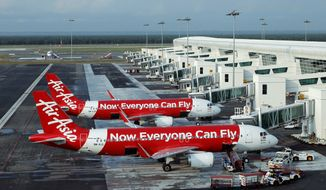 An AirAsia plane with 162 people on board went missing on Sunday, Dec. 28, 2014, while flying over the Java Sea after taking off from Surabaya, Indonesia for Singapore. The planes in this photo are not the plane that went missing while flying from Indonesia to Singapore but one of the same models. (AP Photo/Lai Seng Sin)