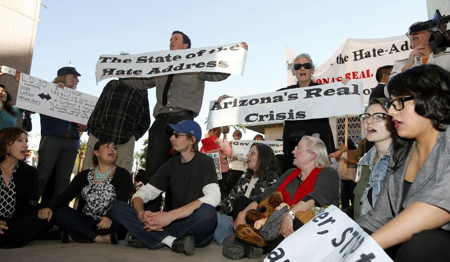 In this Jan. 13, 2014, file photo, immigration rights protesters sit out in front of the House of Representatives after then-Arizona Gov. Jan Brewer gave her State of the State address at the Arizona Capitol, in Phoenix. (AP Photo/Ross D. Franklin, File)