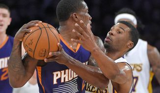Phoenix Suns guard Eric Bledsoe, left, tries to pass past Los Angeles Lakers guard Ronnie Price during the first half of an NBA basketball game, Sunday, Dec. 28, 2014, in Los Angeles. (AP Photo/Mark J. Terrill)