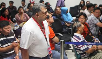 AirAsia Group CEO Tony Fernandes, center, walks past the relatives of the passengers of AirAsia flight QZ8015 at Juanda International Airport in Surabaya, East Java, Indonesia, Sunday, Dec. 28, 2014. A massive sea search was underway for the AirAsia plane that disappeared Sunday while flying from Indonesia to Singapore through airspace possibly thick with dense storm clouds, strong winds and lightning, officials said. (AP Photo/Trisnadi)