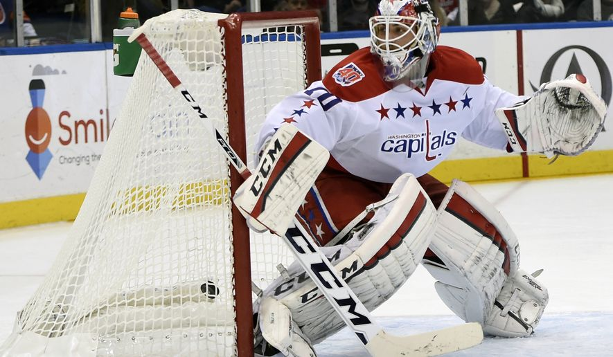 The puck shot by New York Islanders defenseman Lubomir Visnovsky (11) gets past Washington Capitals goalie Braden Holtby (70) to score in the second period of an NHL hockey game at Nassau Coliseum on Monday, Dec. 29, 2014, in Uniondale, N.Y. (AP Photo/Kathy Kmonicek)