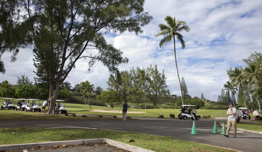FILE -In this Dec. 24, 2014 file photo, President Barack Obama drives away from the 18th hole in a golf cart, far right, with Malaysian Prime Minister Najib Razak as they play golf at Marine Corps Base Hawaii's Kaneohe Klipper Golf Course in Kaneohe, Hawaii. A couple getting married near President Barack Obama's vacation spot in Hawaii learned the hard way that the big day rarely goes exactly as planned. The bride and groom _ both U.S. Army captains _ were scheduled to tie the knot Sunday at Kaneohe Klipper Golf Course, a military course with ocean views near Obama's rented vacation home in Kailua. But on Saturday, they were told they'd have to move their wedding away from the 16th hole because Obama and his friends planned to golf.(AP Photo/Jacquelyn Martin, File)