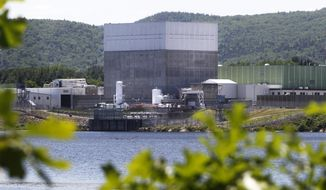 In this June 19, 2013 file photo, the Vermont Yankee Nuclear Power Station sits along the banks of the Connecticut River in Vernon, Vt. Its owner, Entergy Corp., said it is closing the plant for economic reasons, and is expected to be disconnect from the regional power grid. (AP Photo/Toby Talbot, File)