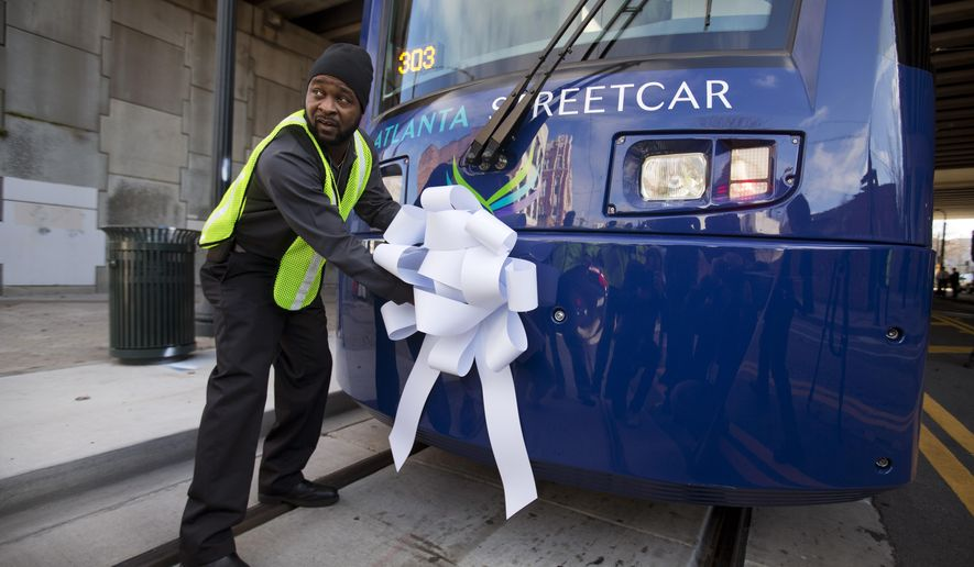 Operations and Maintenance Supervisor Darius Hall places a ribbon on an Atlanta Streetcar before it makes its inaugural trip through downtown, Tuesday, Dec. 30, 2014, in Atlanta. The inaugural journey marks the first time streetcars have regularly traversed Atlanta streets since 1949. The official launch of the new streetcar happened during a grand opening ceremony in Woodruff Park downtown, where dignitaries spoke, pastors blessed it with prayers and onlookers snapped photos on cellphones.  (AP Photo/David Goldman)