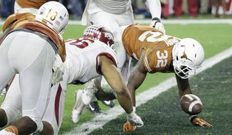 Texas's Johnathan Gray (32) fumbles in the end zone in front of Arkansas's Trey Flowers during the first half of the Texas Bowl NCAA college football game Monday, Dec. 29, 2014, in Houston. Arkansas recovered in the end zone for a touchdown. (AP Photo/David J. Phillip)