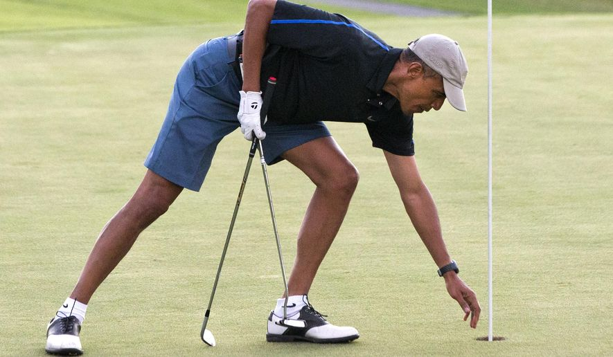 President Obama reaches for his ball after making par while golfing on Dec. 29, 2014, on the 18th hole of the Mid Pacific Country Club in Kailua, Hawaii. (Associated Press) ** FILE **