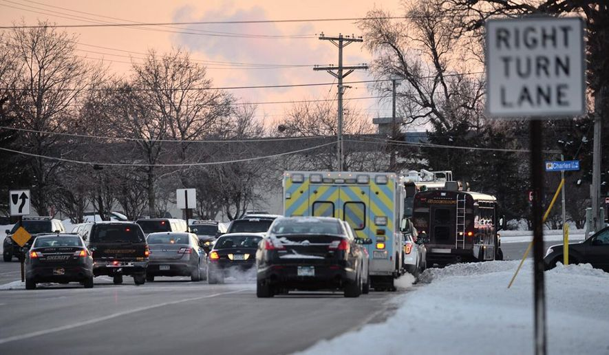 Law enforcement officers engage in a standoff Tuesday, Dec. 30, 2014, in Fridley, Minn. Police evacuated an apartment building in Fridley because of the standoff, which has now ended. (AP Photo/The Star Tribune, Aaron Lavinsky)  MANDATORY CREDIT; ST. PAUL PIONEER PRESS OUT; MAGS OUT; TWIN CITIES TV OUT